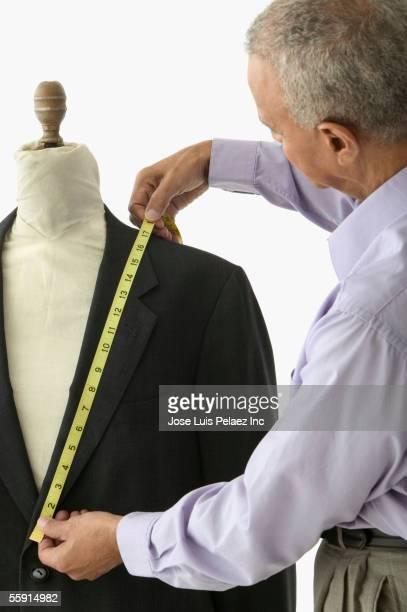 Rear view of a mature man measuring a blazer