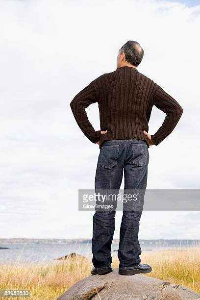 rear view of a mature man standing on a rock with arms akimbo - handen op de heupen stockfoto's en -beelden