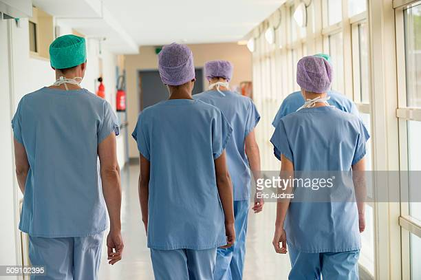 rear view of a medical team walking in the corridor of a hospital - infirmière photos et images de collection
