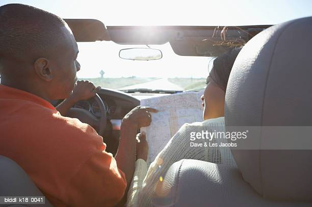 Rear view of a mid adult couple in a convertible car and looking at a road map