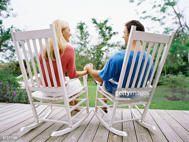 rear view of a mid adult couple sitting on rocking chairs - rocking chair stock pictures, royalty-free photos & images