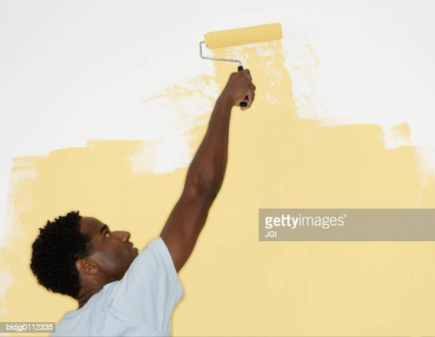 Rear view of a mid adult man painting a wall with a paint roller