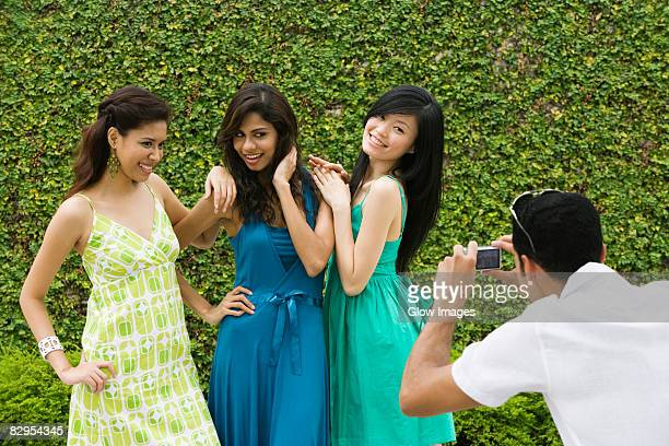 Rear view of a mid adult man photographing three young women with a digital camera