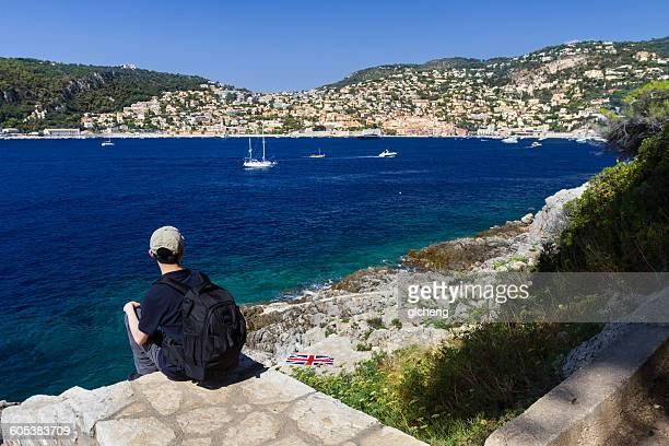 Rear view of a mid adult man sitting looking at view, Cap Ferrat, Cote d'Azur, France