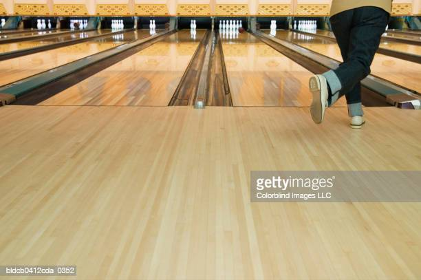 rear view of a mid adult person bowling - bowling alley stock pictures, royalty-free photos & images