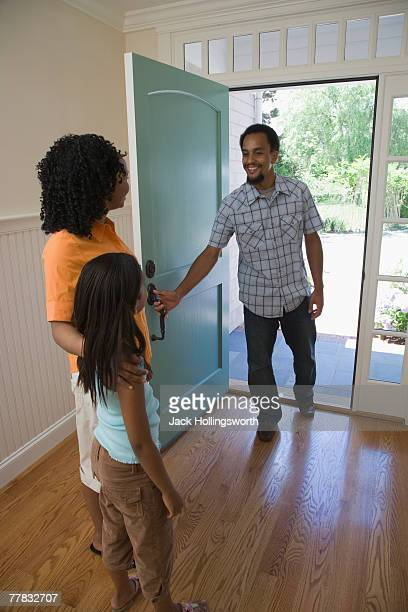 Rear view of a mid adult woman and her daughter greeting a young man at the front door