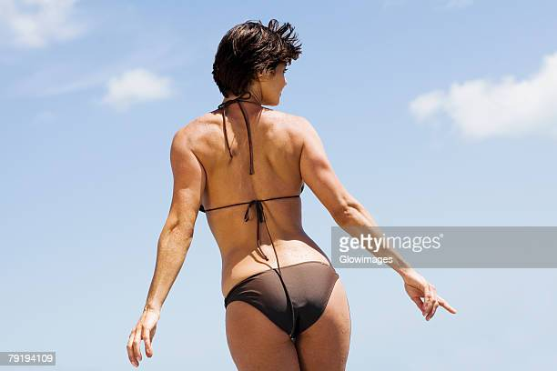 rear view of a mid adult woman posing on the beach - beautiful female bottoms stock pictures, royalty-free photos & images