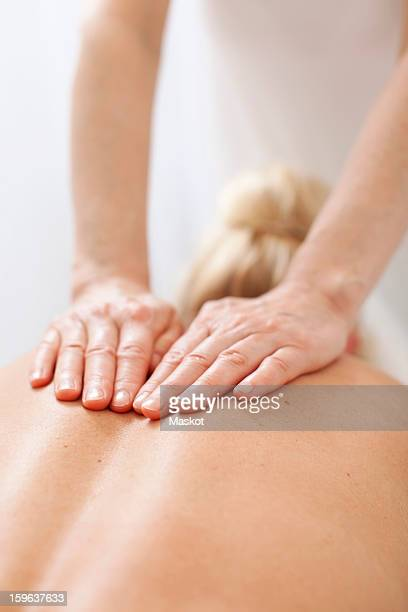 Rear view of a mid adult woman receiving back massage from mature therapist at health spa