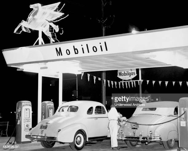 Rear view of a Mobil gas station attendant filling a car with fuel, California, late 1930s.