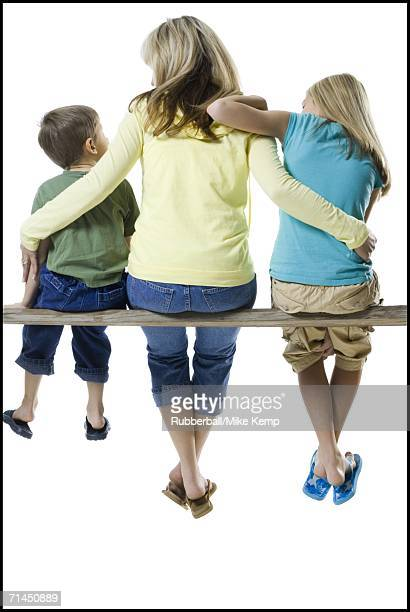 Rear view of a mother and her two children sitting on a wooden plank