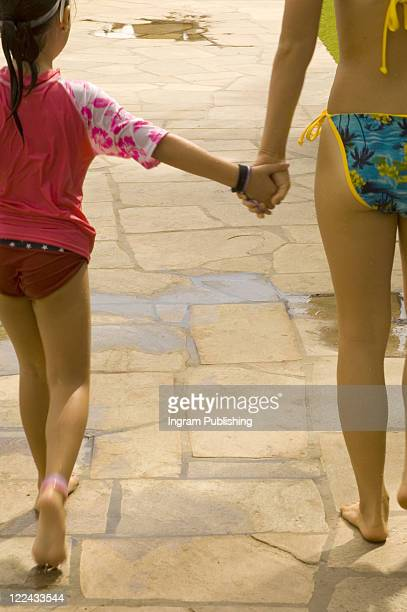 rear view of a mother holding her daughter's hand - little girls bare bum stock pictures, royalty-free photos & images