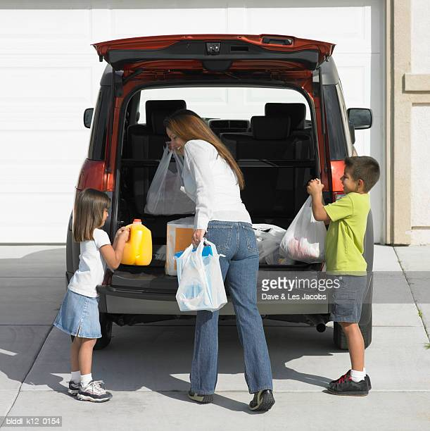 Rear view of a mother with her son and daughter unloading shopping bags from a car