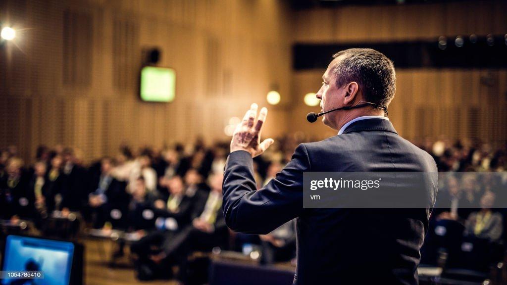 Rear view of a motivational coach giving a speech : Stock Photo