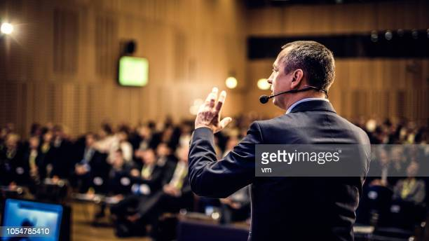 rear view of a motivational coach giving a speech - conference stock pictures, royalty-free photos & images