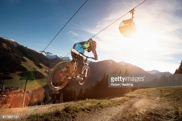 'Rear view of a mountain biker jumps over a bump, Saalbach-Hinterglemm, Zell am See, Salzburg, Austria'