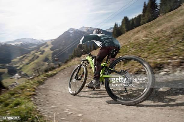 'Rear view of a mountain biker riding downhill, Saalbach-Hinterglemm, Zell am See, Salzburg, Austria'