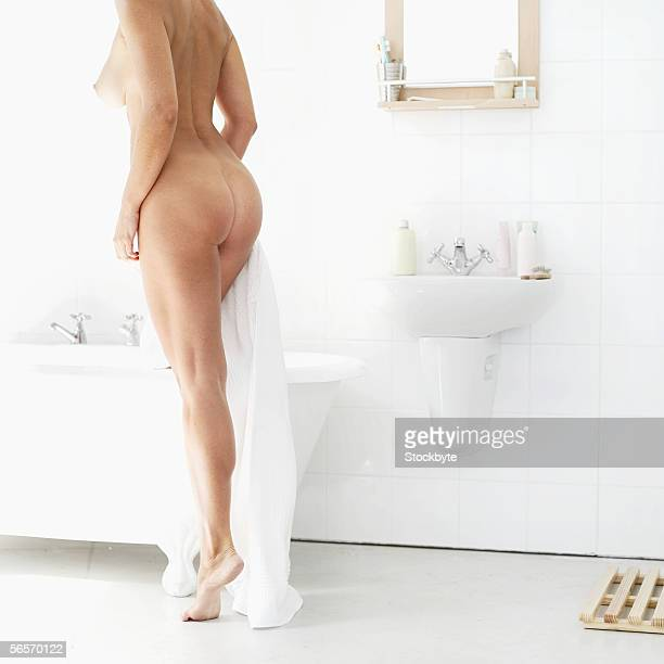 rear view of a naked woman stepping into a bathtub
