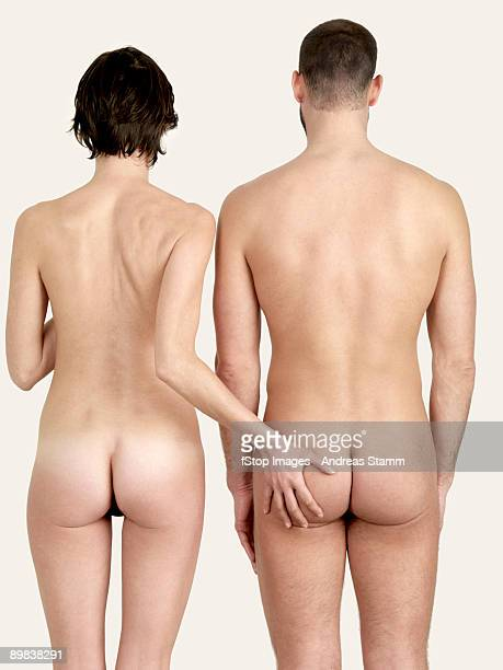 rear view of a naked woman touching a naked man's bottom - male female nude stock pictures, royalty-free photos & images
