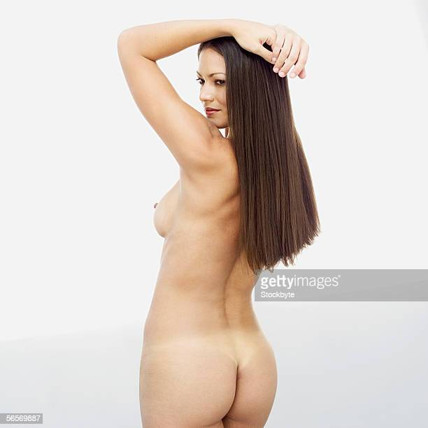 rear view of a naked young woman with her hands above her head