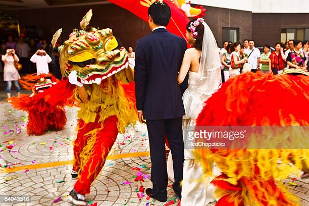 Rear view of a newlywed couple in a traditional ceremony, Qingdao, Shandong Province, China