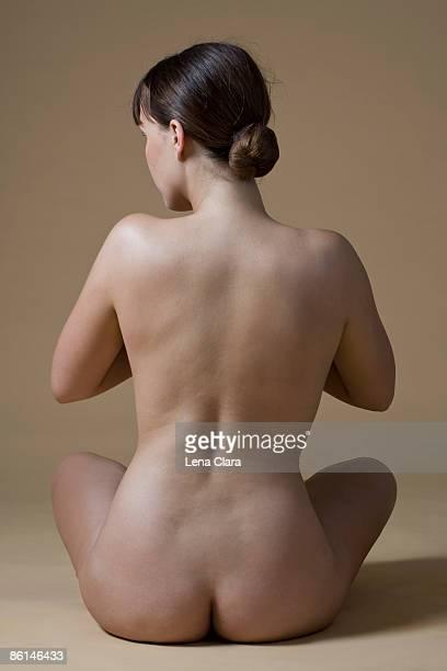 rear view of a nude woman sitting crossed-legged - femme brune de dos photos et images de collection