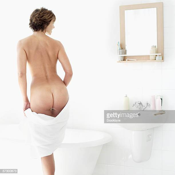 Rear view of a nude young woman dropping towel and into a bathtub