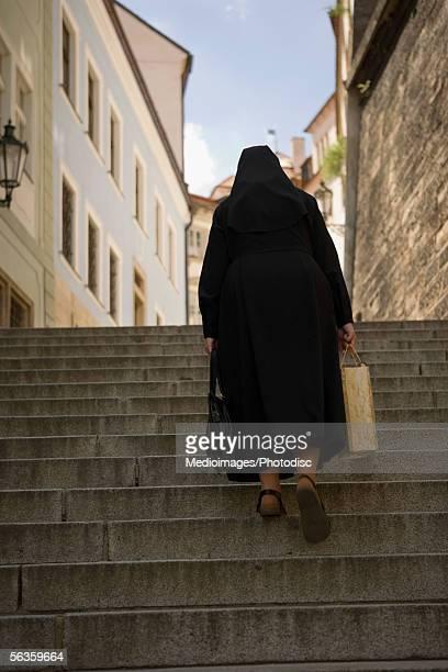 Rear view of a nun climbing stairs, Prague, Czech Republic