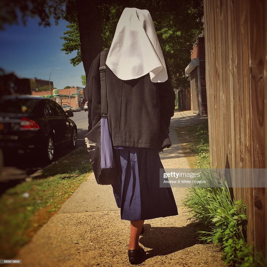 Rear View Of A Nun Walking On Pathway : Stock Photo