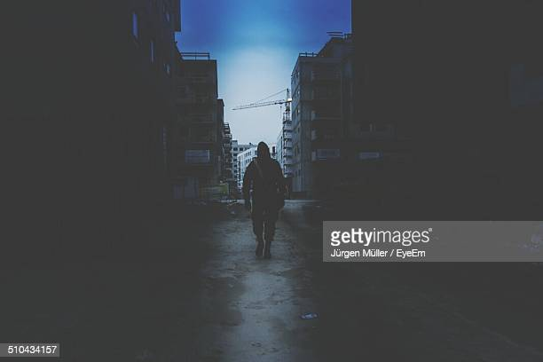 Rear view of a person walking on road along dark buildings