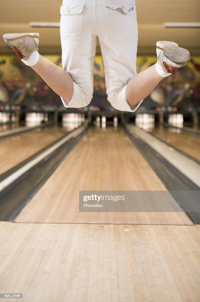 Rear view of a person's feet jumping at a bowling alley : Foto de stock