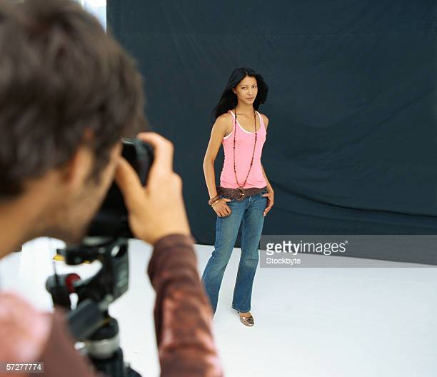 Rear view of a photographer photographing a young woman