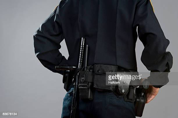 rear view of a police officer carrying weapons - police uniform stock pictures, royalty-free photos & images