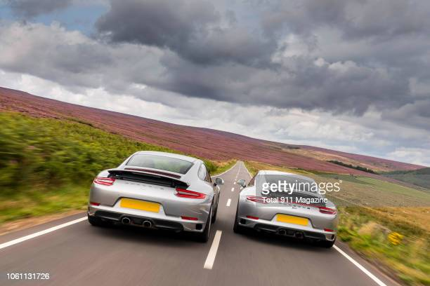 Rear view of a Porsche 9912 Carrera and a Porsche 9112 Carrera 4 GTS sports car driving in the Peak District on August 24 2017