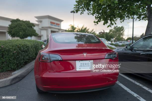 Rear view of a red Tesla Model 3 electric car from Tesla Motors with a license plate reading Zero Emissions under a dramatic sky in the San Francisco...