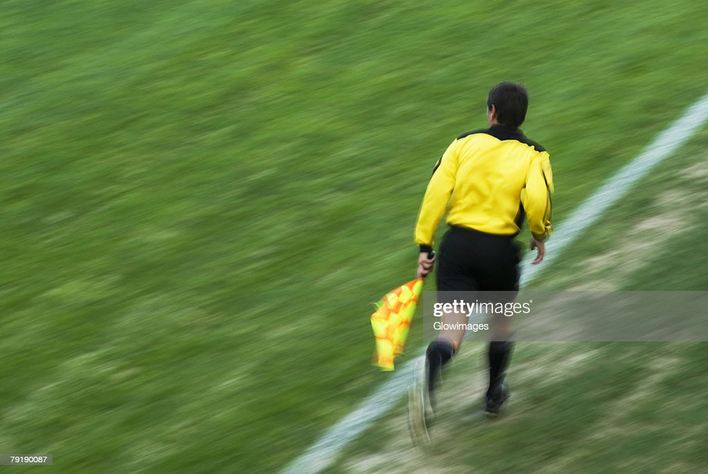 Rear view of a referee running on a football pitch : Stock Photo