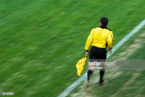 rear view of a referee running on a football pitch - referee stock photos and pictures