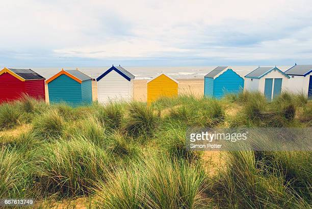 Rear view of a row multi-coloured beach huts in sand dunes, Southwold, Suffolk, United Kingdom