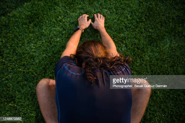 rear view of a runner man stretching on the grass field of a running track - extra long stock pictures, royalty-free photos & images