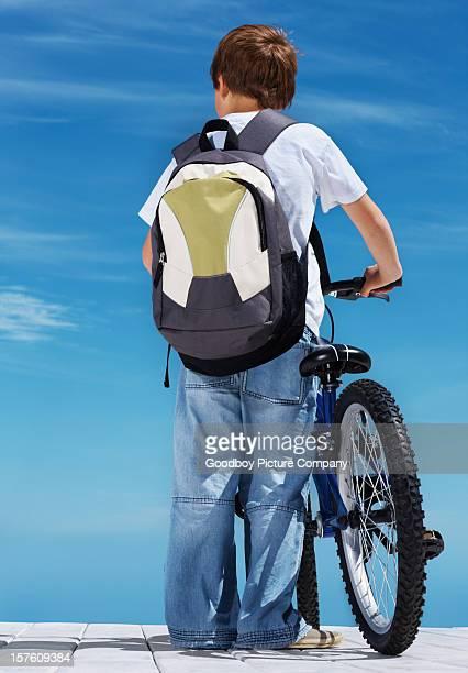 Rückansicht einer Schule Junge mit Fahrrad