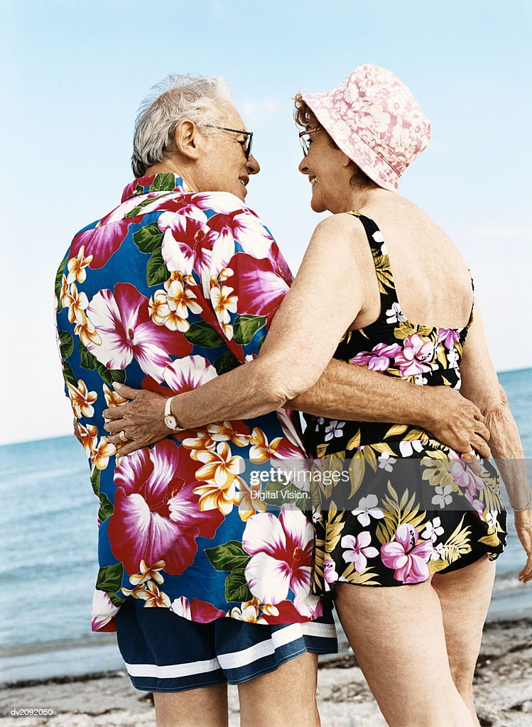Rear View of a Senior Couple in Colourful Swimwear Standing on the Beach With Their Arms Around Each Other : Stock Photo