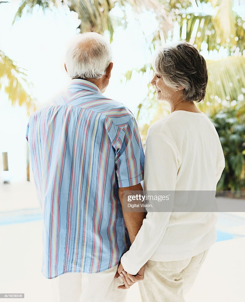Rear View of a Senior Couple in Summer Clothes Standing Outdoors Holding Hands : Stock Photo