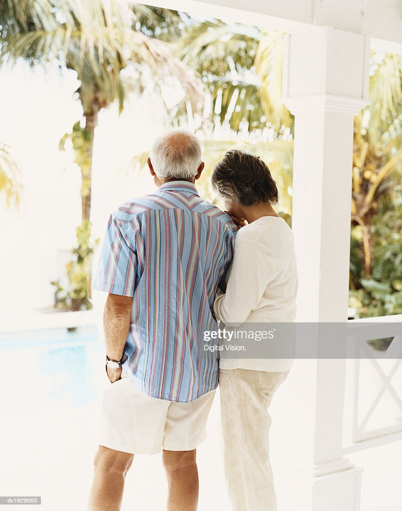 Rear View of a Senior Couple in Summer Clothing Standing on Their Porch : Stock Photo