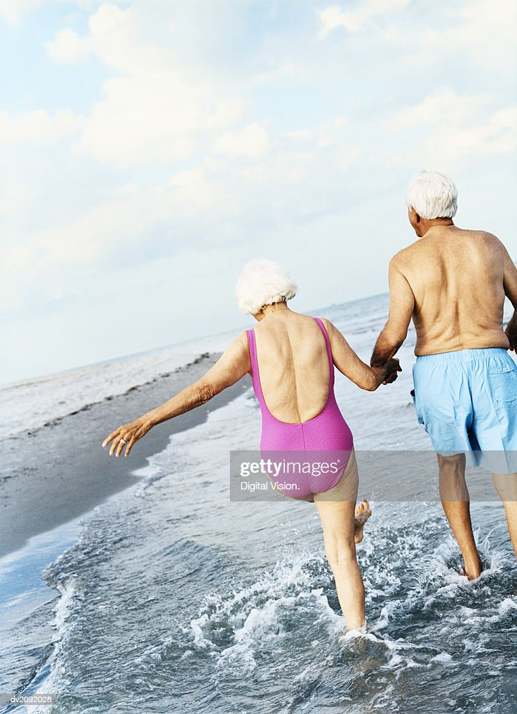Rear View of a Senior Couple Walking in the Surf and Holding Hands : Stock Photo