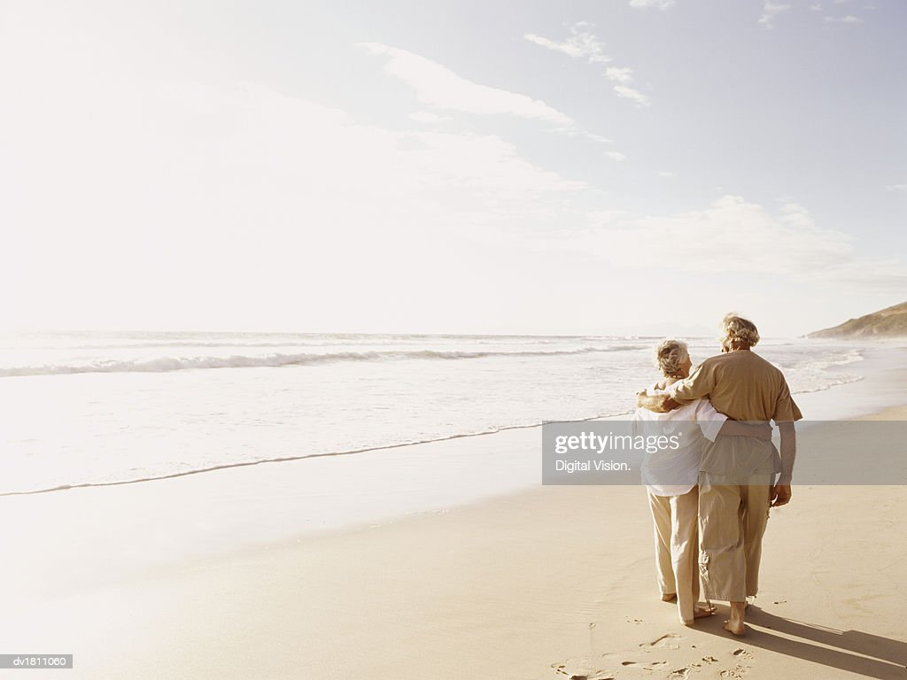 Rear View of a Senior Couple Walking on a Beach With Their Arms Around Each Other : Stock Photo