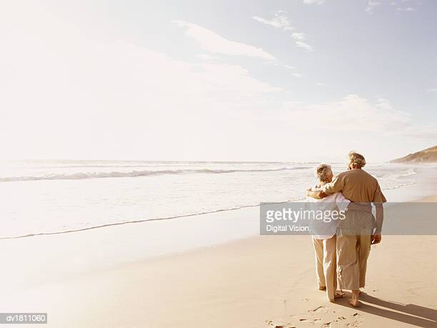 rear view of a senior couple walking on a beach with their arms around each other - overexposed stock pictures, royalty-free photos & images