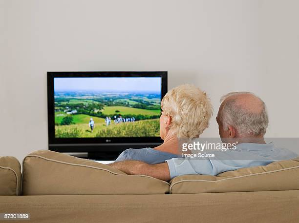 Rear view of a senior couple watching tv