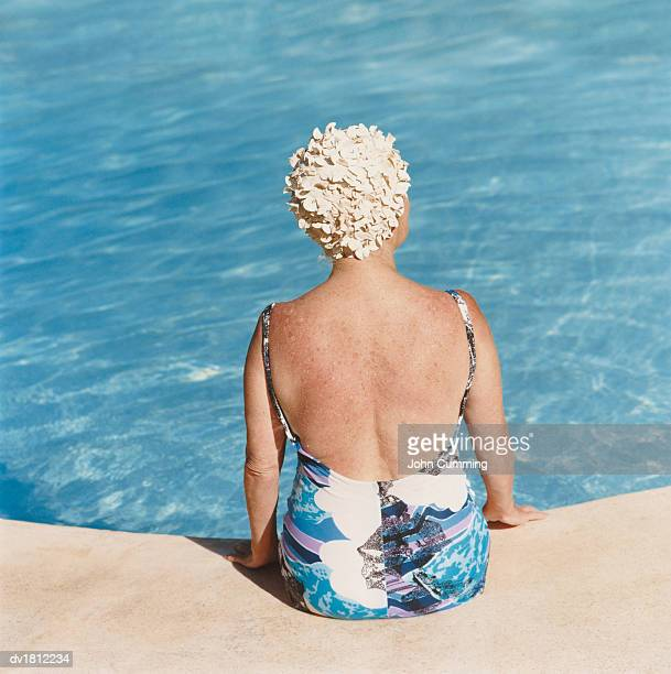 Rear View of a Senior Woman Sitting Poolside