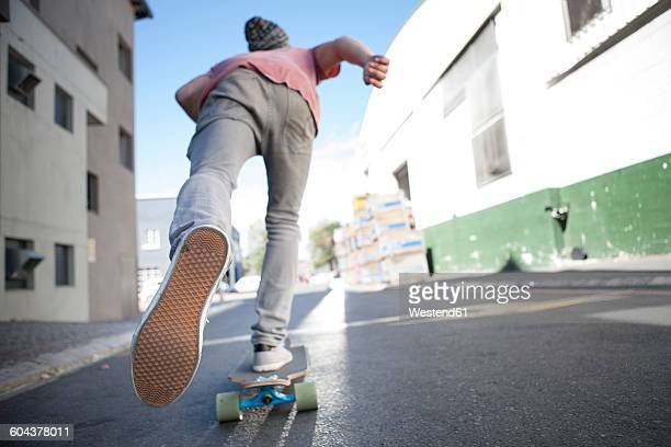 rear view of a skateboarder on the street - 靴底 ストックフォトと画像