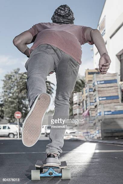 Rear view of a skateboarder on the street
