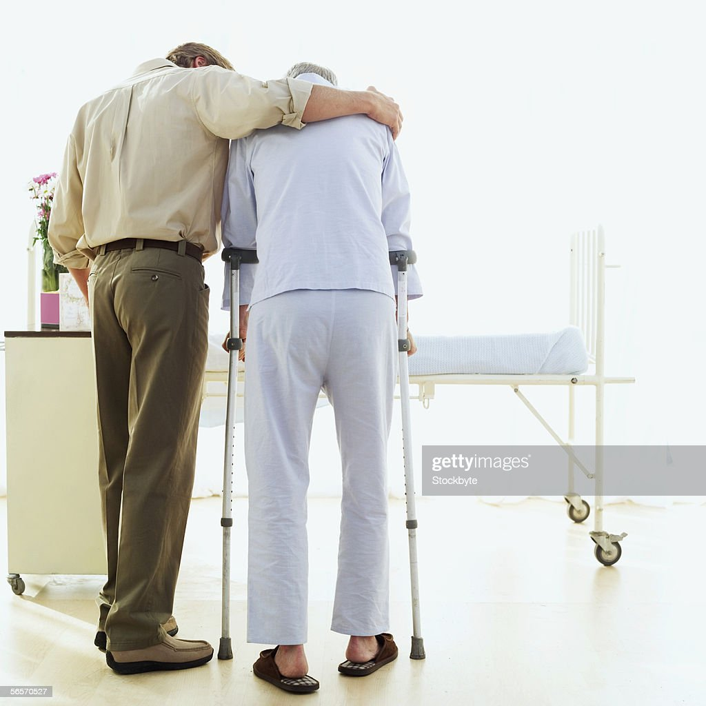 rear view of a son helping his father walk with crutches : Stock Photo